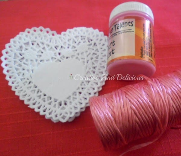 Craft supplies needed to make a valentines day doily banner and vase