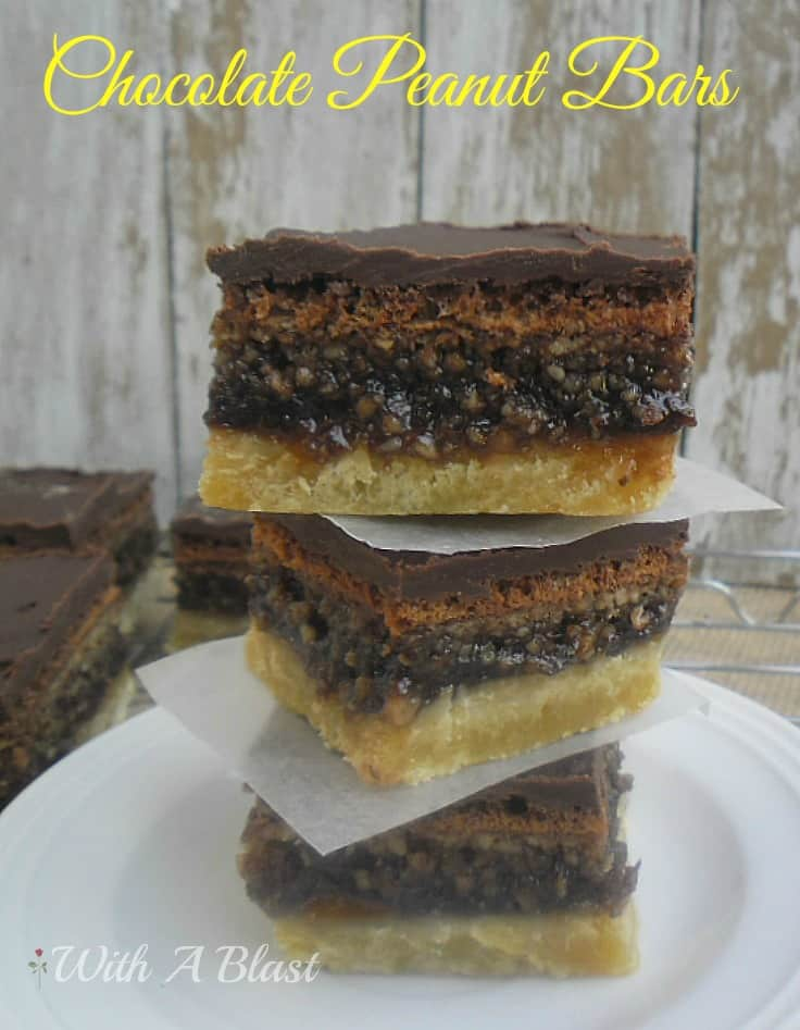 Gooey Chocolate Peanut Bars ~ Layers of pure delight ~ cookie crust with a gooey chocolate/peanut filling and topped with a rich chocolate icing #SweetTreats #PartySnacks #Desserts #PeanutBars www.WithABlast.net