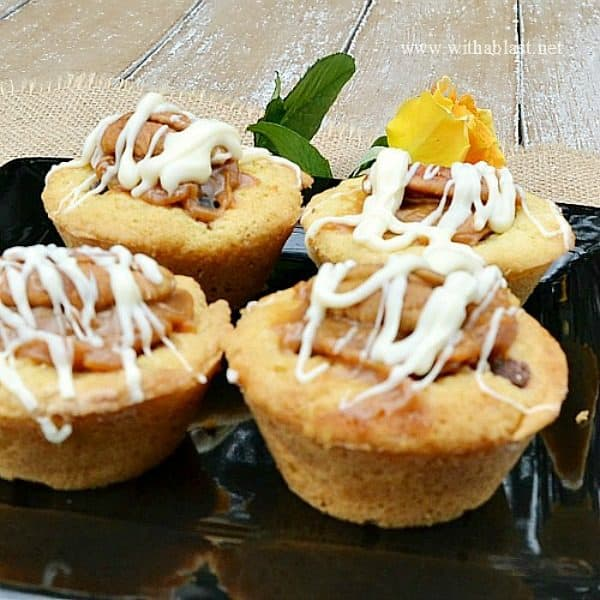 Quick, easy and delicious Cookie Cups filled with Chocolate Chips, chopped Pecans, Caramel and topped with another Pecan Nut and drizzled with White Chocolate